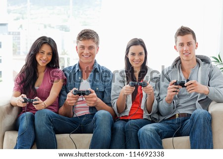 A smiling group of friends sit on the couch with controllers playing a game together #114692338