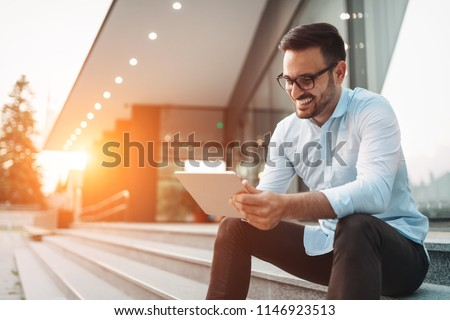 Portrait of businessman in glasses holding tablet #1146923513