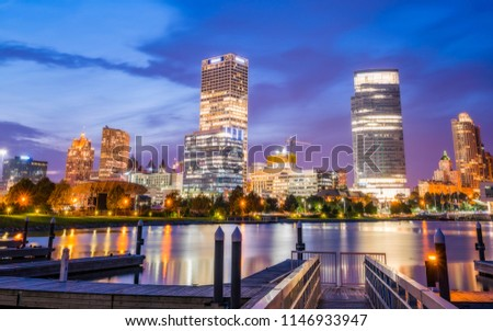milwaukee skyline at night with reflection in lake michigan.