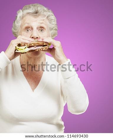 senior woman eating a healthy sandwich against a pink background #114693430