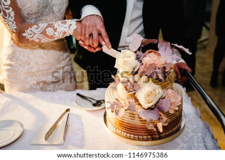 Bride and a groom is cutting their rustic wedding cake on wedding banquet. Hands cut the cake with delicate pink flowers.