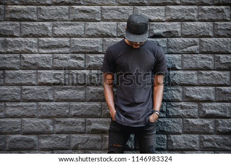 Handsome african american man in blank black t-shirt standing against brick wall Royalty-Free Stock Photo #1146983324