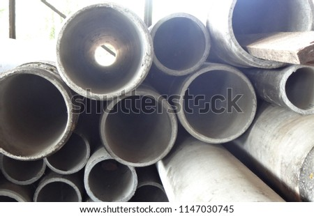 Reinforced concrete pipes of different diameters stacked on top of each other. #1147030745