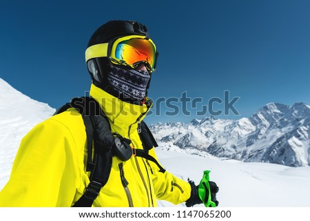 Close-up portrait of a skier in a mask and helmet with a closed face against a background of snow-capped mountains and blue sky #1147065200