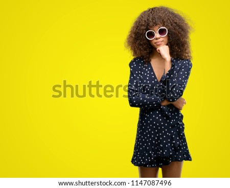 African american woman with sunglasses and summer dress serious face thinking about question, very confused idea #1147087496
