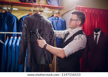 tailor cuts and sews a suit. A young man in the tailoring shop makes men's clothing. Custom-made clothing workshop. holds in her hand an electric iron. wet-heat treatment #1147156553