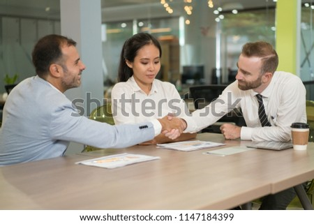 Business people shaking hands at desk in office. Multiethnic businesspeople meeting and sitting with modern blurred interior in background. Agreement concept. #1147184399