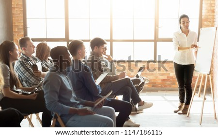 Learning foreign language. Cheerful woman teacher near whiteboard explaining rules to group of students at loft classroom, copy space #1147186115