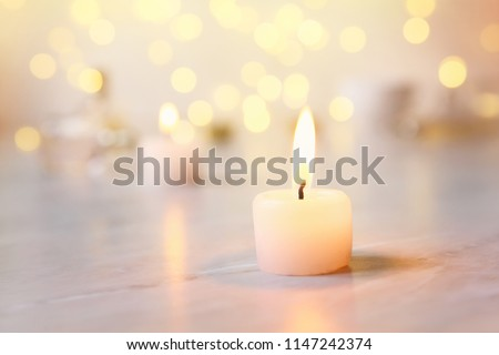 Small candle with light yellow spots on light background Royalty-Free Stock Photo #1147242374