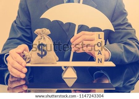 Loan protection insurance / financial support concept : Businessman holds umbrella guards dollar money bags on a simple balance scale, depicts protection policy that protects the insurer from default #1147243304