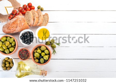 Green olives and black olives, oil, bread, cheese and snacks. Italian cuisine. On a white wooden table. Top view. Free space for text. #1147251032