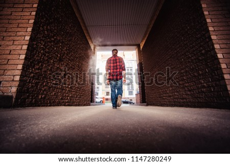 Lifestyle portrait concept. Bearded strolls on the streets of the city among the houses. stroll through the brick arch of the house close #1147280249