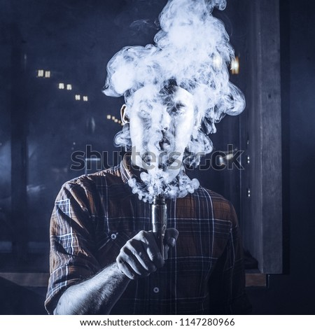 Punk hipster man is smoking a mechanical vape device. Toned image. The concept of popularization of vaping. Ecig rapairing process with cloud of steam from vaping device #1147280966