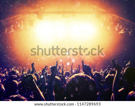 Concert audience under a rain of dust particles and confetti, stage is visible ahead #1147289693