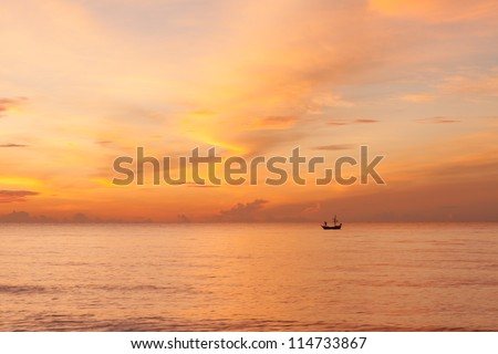 A beautiful morning sky with a fisherman on a boat in the sea, a beautiful orange sky with cloud reflection on the sea. Taken at Hua hin beach, Prachuabkhirikhan, Thailand. #114733867