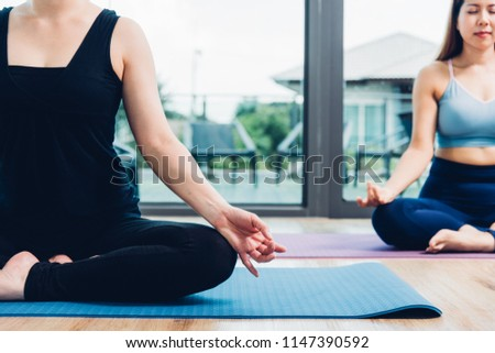 Young woman doing sitting meditation yoga in fitness gym #1147390592