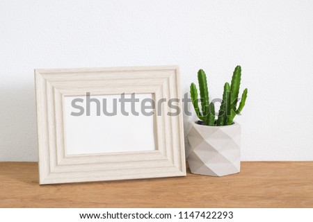 Frame photo with cactus in pot. Modern style home decor #1147422293