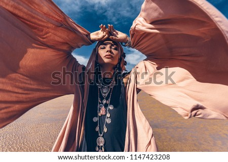 young stylish woman with fashionable boho accessories on the beach windy time #1147423208