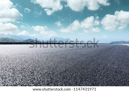 Asphalt road and beautiful mountain scenery under the blue sky