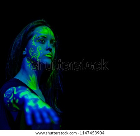 Female caucasian model with plant inspired green blacklight paint glowing. Shallow focus leaves the focus on the face #1147453904