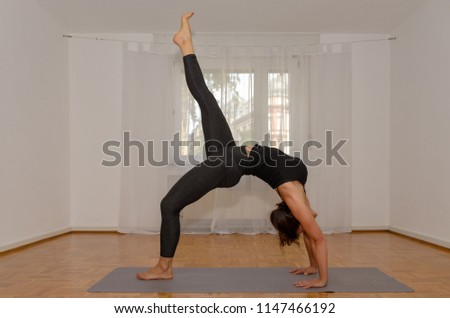 Sporty woman working out at home on a mat on a wooden floor doing the yoga position wheel in a healthy active lifestyle and fitness concept #1147466192