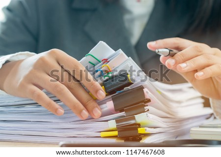 Accounting planning budget concept : Business woman offices working for arranging documents unfinished stack of document papers with pen, calculator, clip papers on busy office desk #1147467608