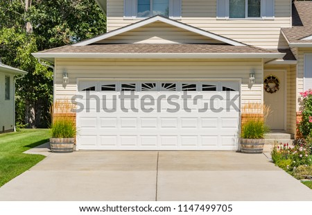 A perfect neighbourhood. Family house with wide garage door and concrete driveway in front #1147499705