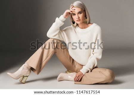 attractive fashionable woman posing in white trendy sweater, beige pants and autumn heels, on grey  Royalty-Free Stock Photo #1147617554