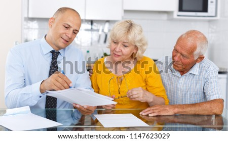 Aged couple signing financial agreement with bank worker at home  #1147623029