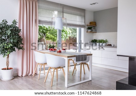 Gray roman shades and a pink curtain on big, glass windows in a modern kitchen and dining room interior with a wooden table and white chairs #1147624868