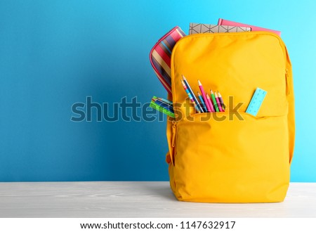Backpack with different colorful stationery on table. Back to school Royalty-Free Stock Photo #1147632917