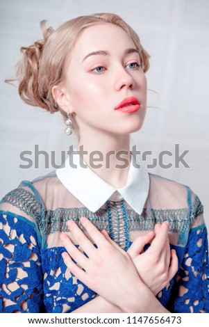 Cute young woman in navy blue dress holding bird cage, spring tender fashion studio shot #1147656473