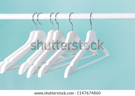 Many wooden white hangers on a rod, isolated on blue turquoise wall background. Store concept, sale, design, empty hanger. Place for text. #1147674860
