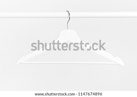 One white wooden hanger without clothes on background of white wall. Soft focus. Store concept, sale, design, empty hanger. #1147674896
