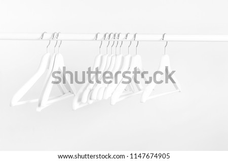Many wooden white hangers on a rod, isolated on white wall background. Store concept, sale, design, empty hanger. Place for text.  #1147674905