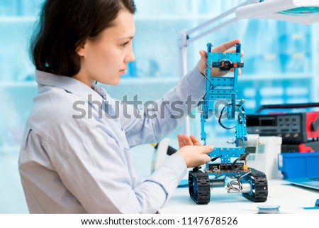 Young woman in CNC and robotics laboratory #1147678526