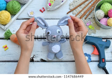 Making rabbit with carrot. Crochet bunny for child. On table threads, needles, hook, cotton yarn. Handmade crafts. DIY concept. Small business. Income from hobby. Royalty-Free Stock Photo #1147686449