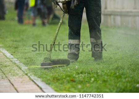 Law mower man trimming grass in the city #1147742351