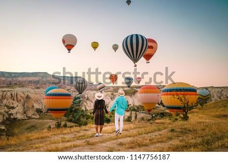happy young couple during sunrise watching the hot air balloons of Kapadokya Cappadocia Turkey #1147756187