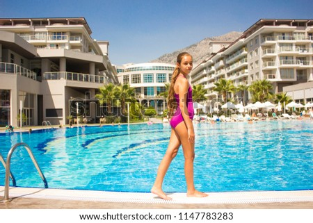 KEMER, ANTALYA, TURKEY - 19 JULY, 2018: Beautiful teenage girl in the purple swimsuit standing at poolside #1147783283