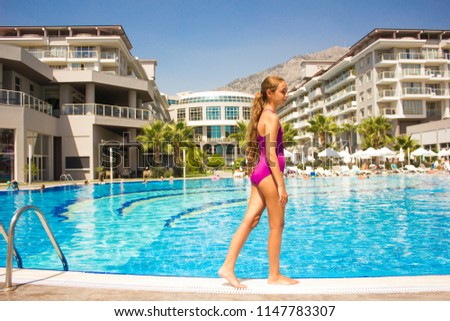 KEMER, ANTALYA, TURKEY - 19 JULY, 2018: Beautiful teenage girl in the purple swimsuit standing at poolside #1147783307