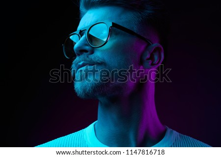 Neon light studio close-up portrait of serious man model with mustaches and beard in sunglasses and white t-shirt  #1147816718