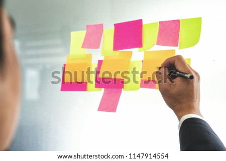Business using post it for notes idea brainstorming strategy of new project on glass wall at office.  #1147914554