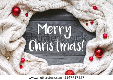 """Christmas card """"Merry Christmas"""" with frame decorated with knitted scarf on grey rough wooden background. Flat lay, top view, copy space. #1147917827"""