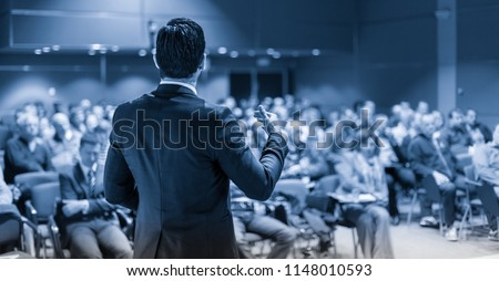 Speaker giving a talk on corporate business conference. Unrecognizable people in audience at conference hall. Business and Entrepreneurship event. Blue toned grayscale image. #1148010593