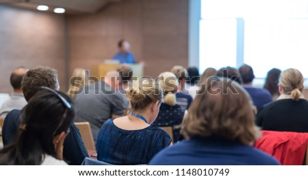 Business and entrepreneurship symposium. Speaker giving a talk at health care workshop meeting. Audience in conference hall. Rear view of unrecognized participant in audience. #1148010749