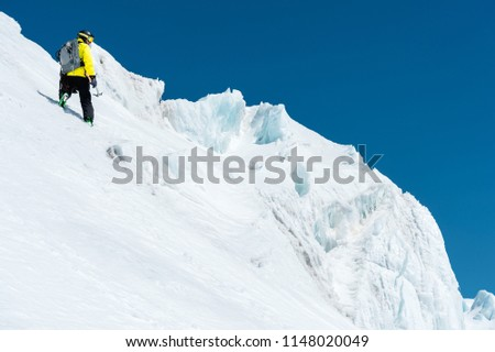 A skier in a helmet and mask with a backpack rises on a slope against the background of snow and a glacier whith ice axe in your hand. Backcountry Freeride #1148020049