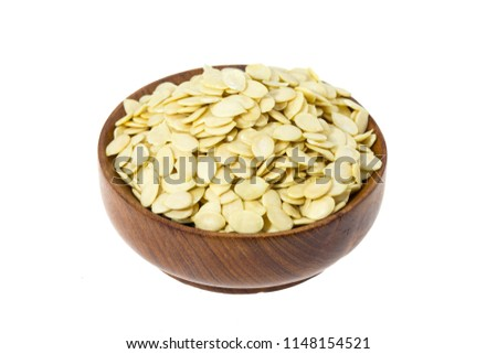 Raw watermelon seeds in a wooden bowl isolated on white backgroun #1148154521