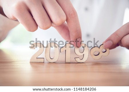 Hands of businessman change wood text 2018 to new year 2019.  #1148184206