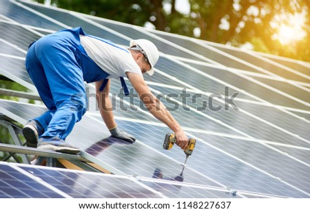 Construction worker connecting photo voltaic panel to solar system using screwdriver on shiny surface and lit by sun green tree background. Alternative energy and financial investment concept. #1148227637